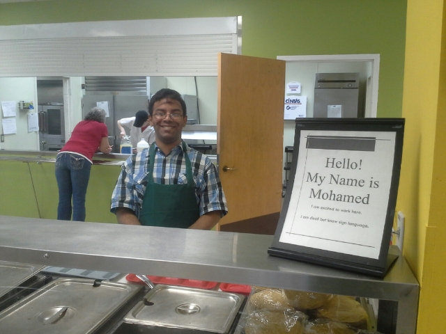 Mohamed smiles proudly at his new job