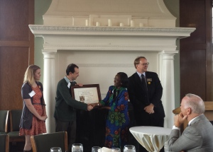 Misha accepts the Warehouse Volunteer Award from Her Excellency Liberata Mulamula